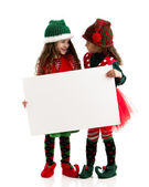 Santas elves hold a blank sign for christmas holiday message — Stok fotoğraf