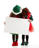 Santas elves hold a blank sign for christmas holiday message — Stock Photo