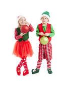 Two young elves carry two large Christmas ornament balls — Stock Photo