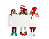 Three of santas elves hold a blank sign ready for your holiday adverstising message. — Stock Photo