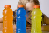 Young girl peers between bottles — Stock Photo