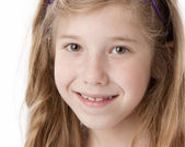 A closeup headshot of a caucasian 8 year old little real girl with long hair and green eyes — Stock Photo