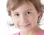 A closeup headshot of a 5 year old caucasian smiling little real gir — ストック写真