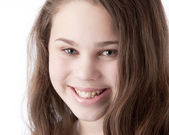 A closeup headshot of a 12 year old caucasian smiling little real girl — Stock Photo