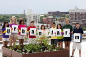 A diverse group of nine children of different ethnicities standing proudly by an urban roof and holding a sign — ストック写真