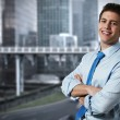 Successful business man with office buildings in the background — Stock Photo