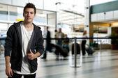 Mladý muž, stojící na letišti na cestách — Stock fotografie