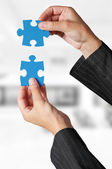 Business concept: Hand holding two pieces of a puzzle — Stock Photo