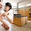 Young happy couple smiling at kitchen of new house — Stock Photo #19290067
