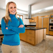 Stock Photo: Young happy woman at her big new kitchen