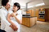 Young happy couple smiling at kitchen of new house — Stock Photo