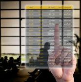 Hand choosing flights pushing a screen interface at the airport — Stock Photo