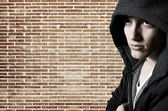 Young cool street style fashion male model posing at brick wall — Stock Photo