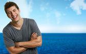 Joven sonriente a hombre relajado en la playa en un día de verano — Foto de Stock