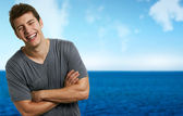 Young smiling relaxed man at the beach in a summer day — Foto de Stock