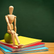 Back to School Series: wooden man sitting over stack of colorful — Stock Photo