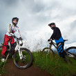 Stock Photo: Two young mriding mountain bike downhill style