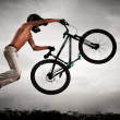 Achievement concept: Man flying high on a bike against the sky — Foto de Stock