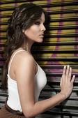 Fashion shot of beautiful young woman posing in a roller shutter — Stock Photo