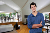 Young man smiling relaxed at his big house — Stock Photo