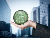 Ecology concept: Hand holding a globe with nature leaves on busi — Stock Photo