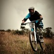 Young man riding a mountain bike downhill style — Stock Photo