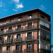 Architecture, brick spanish buildings with terraces and blue sky — Stock Photo