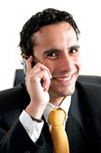 Young business man at office smiles at the phone — Stock Photo
