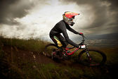 Young man riding a mountain bike downhill style — Stok fotoğraf