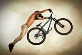Young man flying on his bike: Dirt jump — Fotografia Stock