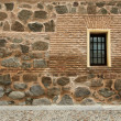 Stone wall with window and street (horizontal) — Stock Photo