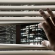 Stock Photo: Mat office opening window blinds and seeing business towers