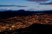 Quito at night with cotopaxi mountain — Stock Photo