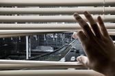Man at office opening window blinds and seeing city streets and — Stock Photo