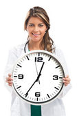 Woman doctor holding clock. Isolated on white — Stock Photo