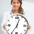 Woman doctor holding clock — ストック写真