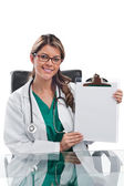 Woman doctor at desk holding white paper — Foto de Stock
