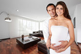 Pregnant couple at new big empty modern department — Stock Photo
