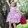 Little girl sits on the tree — Stock Photo