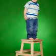 Little boy standing on stairs in studio — Stock Photo