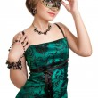 Beautiful girl in green evening dress with necklace and earrings in carnival mask hodling beads — Stock Photo