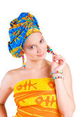 Beautiful smiling girl in cilorful clothes holding her earring — Stock Photo