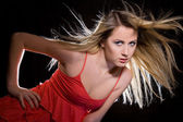 Portrait of blonde girl in red dress with flying hair — Stock Photo