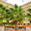 Big palm tree in front of a hotel under blue sky - Stock Photo