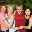Royalty-Free Stock Photo: Four smiling happy friends holding each other in the park