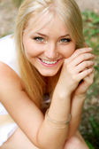 Blonde smiling girl in the park — Stock Photo