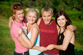 Four smiling happy friends holding each other in the park — Stock Photo