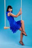 Dívka v modrých šatech na houpačky — Stock fotografie
