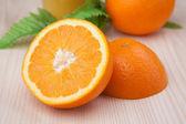 Half of fresh orange on wooden table — Stock Photo