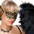 Beautiful girl  with necklace and earrings  in carnival mask hodling fan — Stockfoto